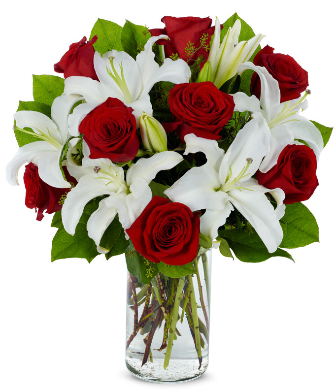 White Stargazer lilies and red roses in a cylinder vase